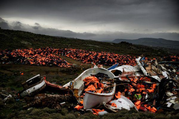 Свалка сломанных лодок и тысяч спасательных жилетов, которыми пользовались беженцы и мигранты во время их переправы через Эгейское море. Фото: Aris Messinis / Agence France Presse