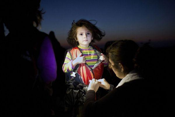 Ребёнку мигрантов помогают снять спасательный жилет после удачного прибытия на греческий остров Кос. Фото:  Aris Messinis /Agence France Presse, август 2015