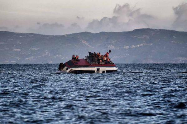 Лодка, заполненная мигрантами, тонет возле берегов острова Лесбос в конце октября. Фото: Aris Messinis /Agence France Presse, октябрь 2015