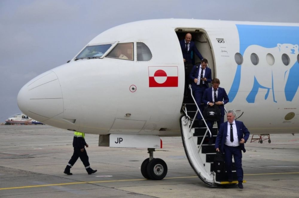 С борта самолёта по трапу спускается руководство команды, в том числе – главный тренер Филлип Коку.