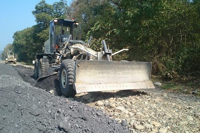 Скальный грунт насыпают на вымытую тайфуном дорогу.