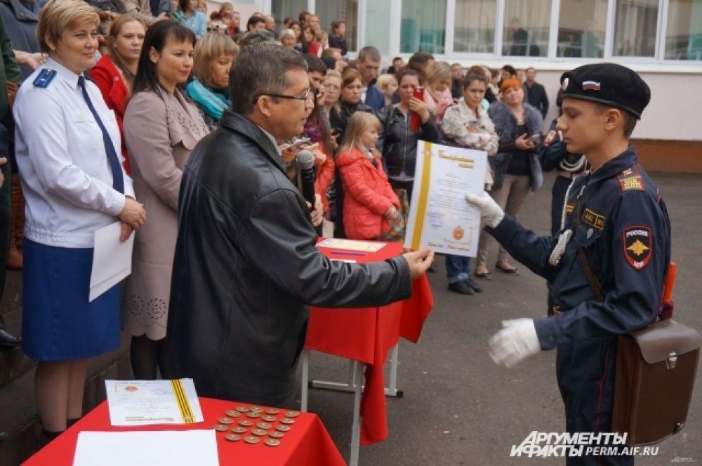Помощник военного комиссара Пермского края по военно-патриотической работе, полковник Владимир Ногин вручает благодарственное письмо курсанту.