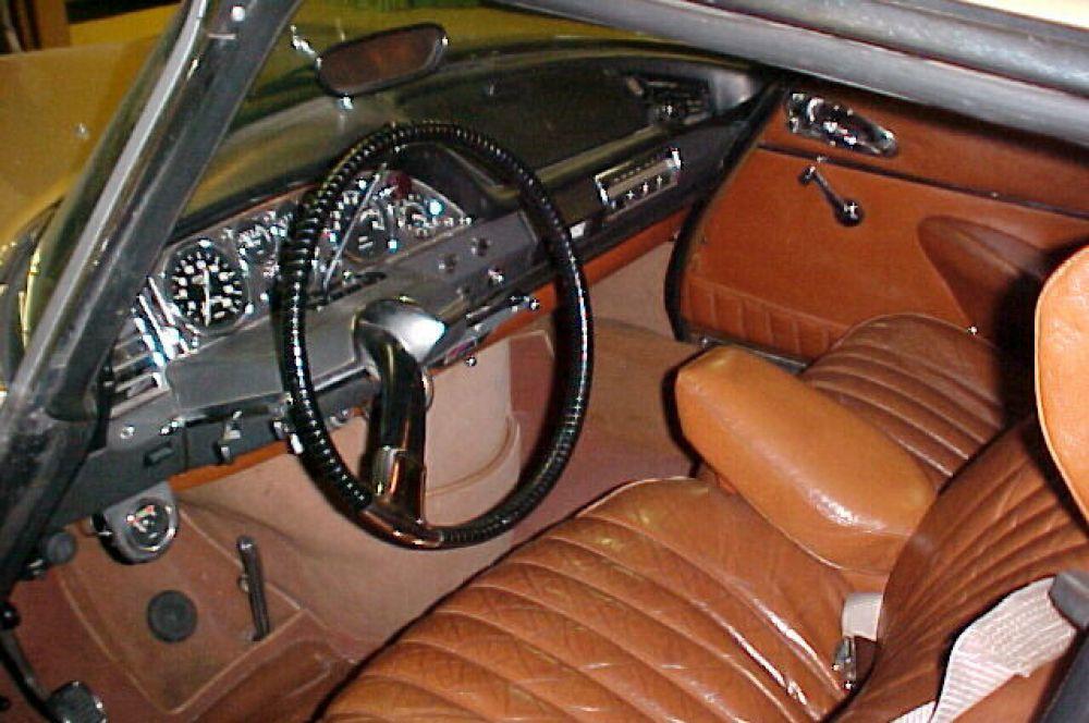 Салон Citroen DS, рулевое колесо с одной спицей, над ним — рычаг переключения передач, внизу видны «палочка» педали газа и «кнопка» педали тормоза, левее — педаль стояночного тормоза.