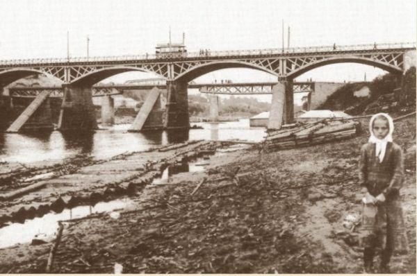 На фото смоленская девочка у берега Днепра на фоне трамвайной ветки, проложенной по мосту.