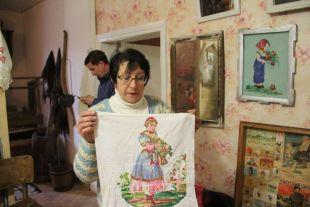 Вера Фомина показывает образцы местного вышивания по европейским образцам.