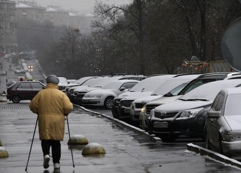 Заснеженные автомобили на одной из улиц в Москве.