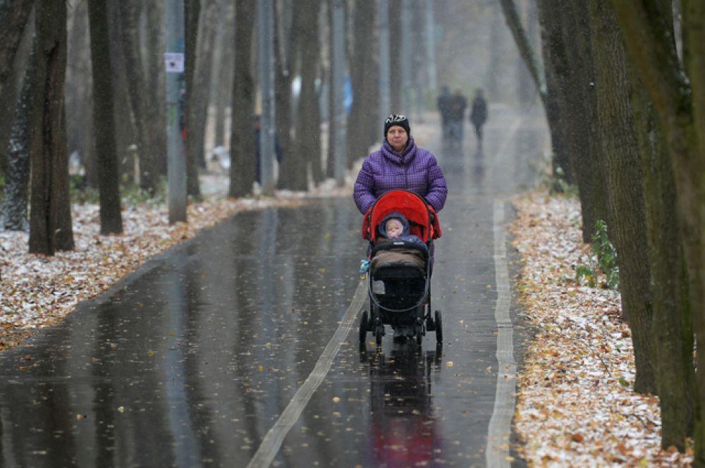Прохожие на аллее в Москве, где выпал первый снег.