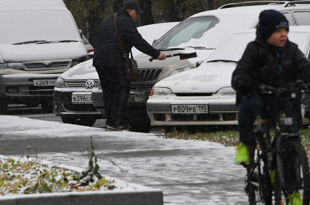 Мужчина очищает свой автомобиль от снега.