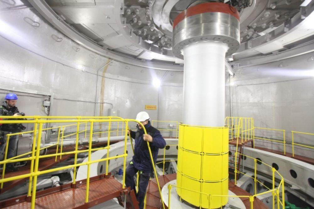 Падающая с высоты плотины вода под напором крутит лопасти турбины генератора. Ротор приходит в движение и вырабатывает переменный ток.