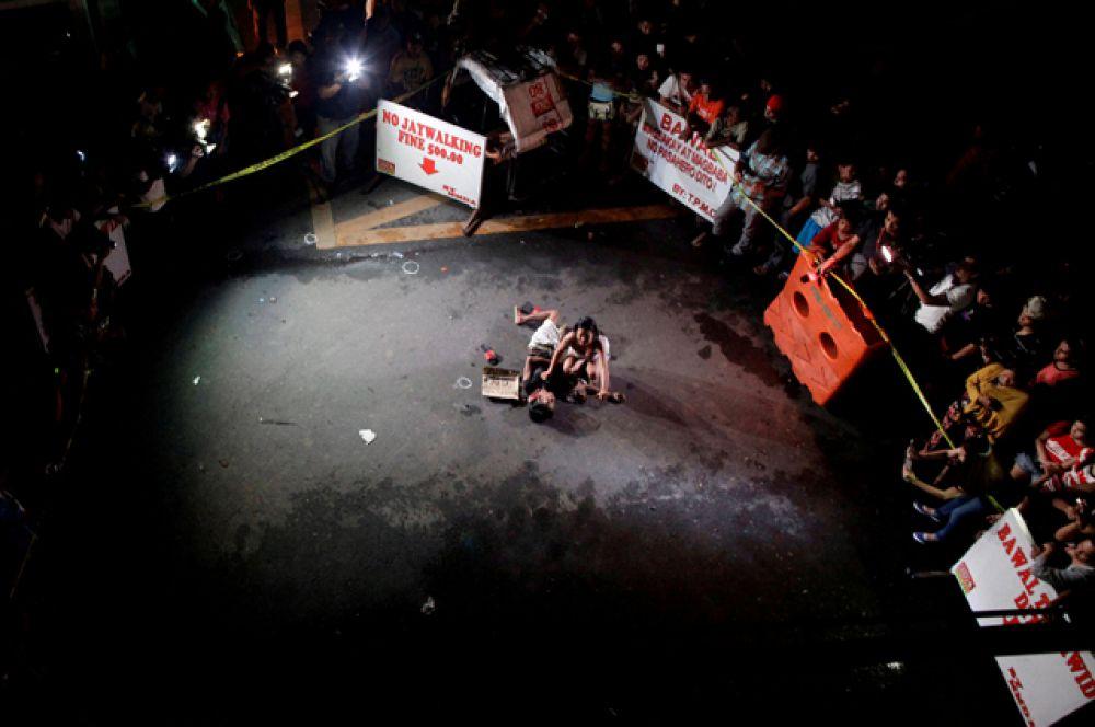 Девушка рыдает над телом своего партнера, который был убит на улице в ходе спецоперации в городе Пасай. Рядом с погибшим найдена картонная табличка с надписью: «Pusher Ako», что переводится как «Я наркодилер».