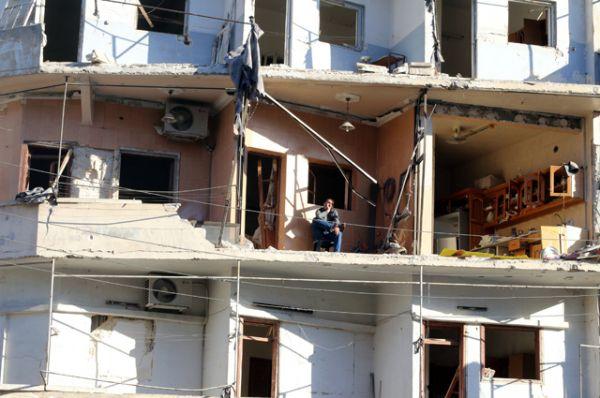 Мужчина на балконе своего разрушенного дома в осажденном районе Аль-Суккари в пригороде Алеппо.