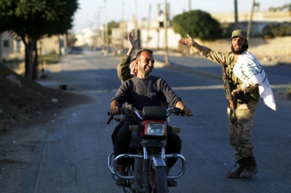 Местный житель едет на мотоцикле в сторону города Дабик на севере Алеппо.