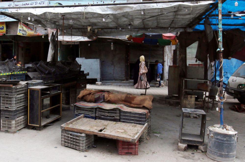 Женщина идет вдоль пустых прилавков в Алеппо.