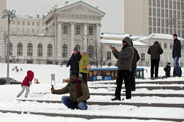 Туристы фотографируются у памятника святому равноапостольному князю Владимиру на Боровицкой площади в Москве.