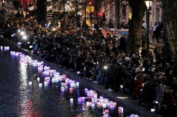 Собравшиеся на траурной церемонии люди зажгли сотни свечей и отпустили их в канал Сен-Мартен в знак памяти о жертвах терактов.