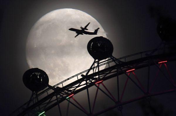 Колесо обозрения London Eye на фоне восходящей Луны в Лондоне.