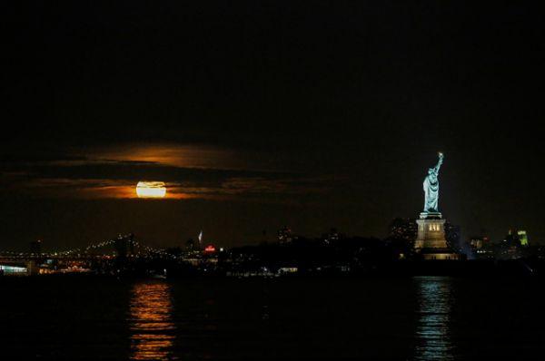 Суперлуние, видное сквозь облака над Нью-Йорке.