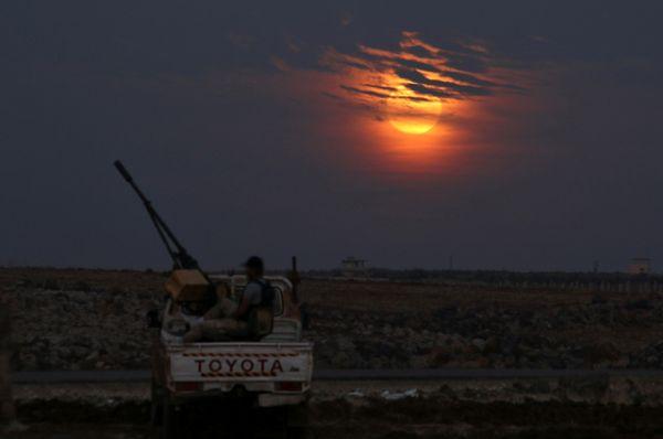 Боец сирийской армии в удерживаемом повстанцами городе Даиль на фоне восходящей Луны.