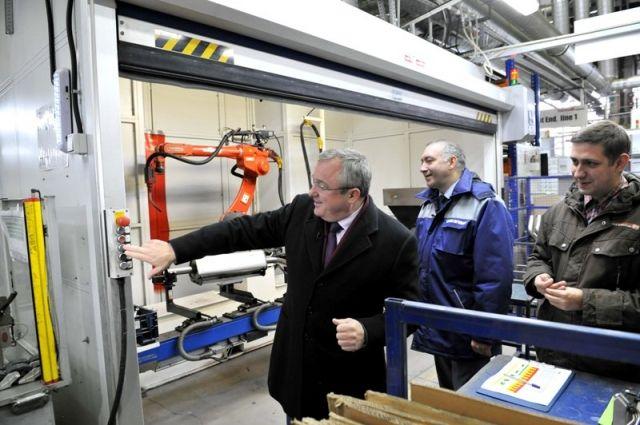 Кирилл Эпштейн (в центре) обучает Игоря Тюрина (слева) работе на автоматизированной линии.
