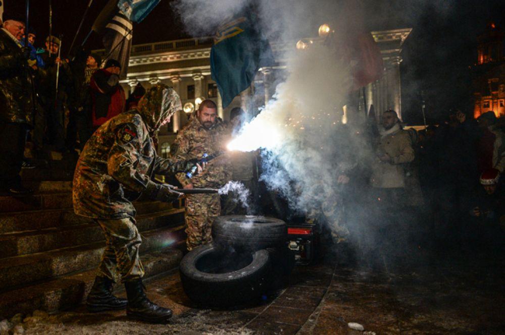 Участники акции, посвященной годовщине начала событий на Майдане, жгут файеры в Киеве.