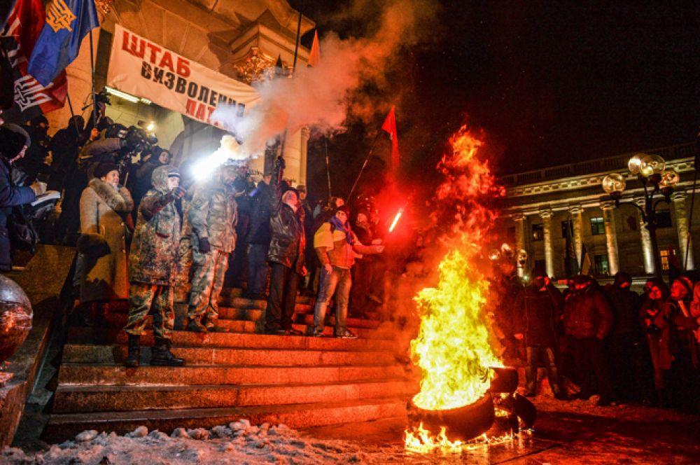 Участники акции, посвященной годовщине начала событий на Майдане, жгут файеры и автомобильные покрышки в Киеве.
