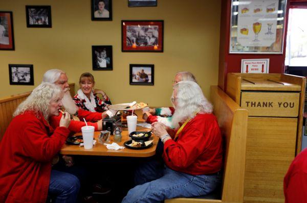 Санты и миссис Клаус наслаждаются обедом в пиццерии во время перерыва.