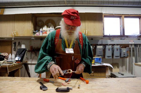 Санта Рэнди Шнайдер из города Маскегон делает игрушку из дерева.