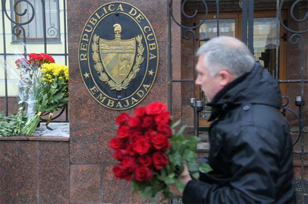 Мужчина несет цветы к посольству Кубы в Москве.