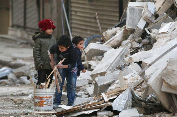 Дети собирают дрова среди обломков зданий и строительного мусора.