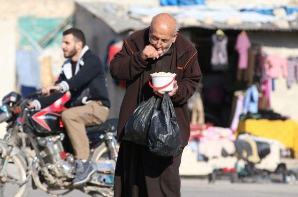 Мужчина ест еду, которая была доставлена в осажденные боевиками районы в качестве гуманитарной помощи.