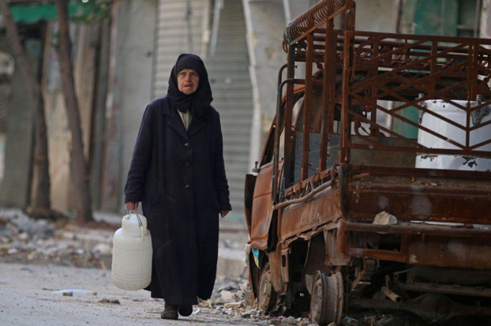 Женщина несет канистру с водой.