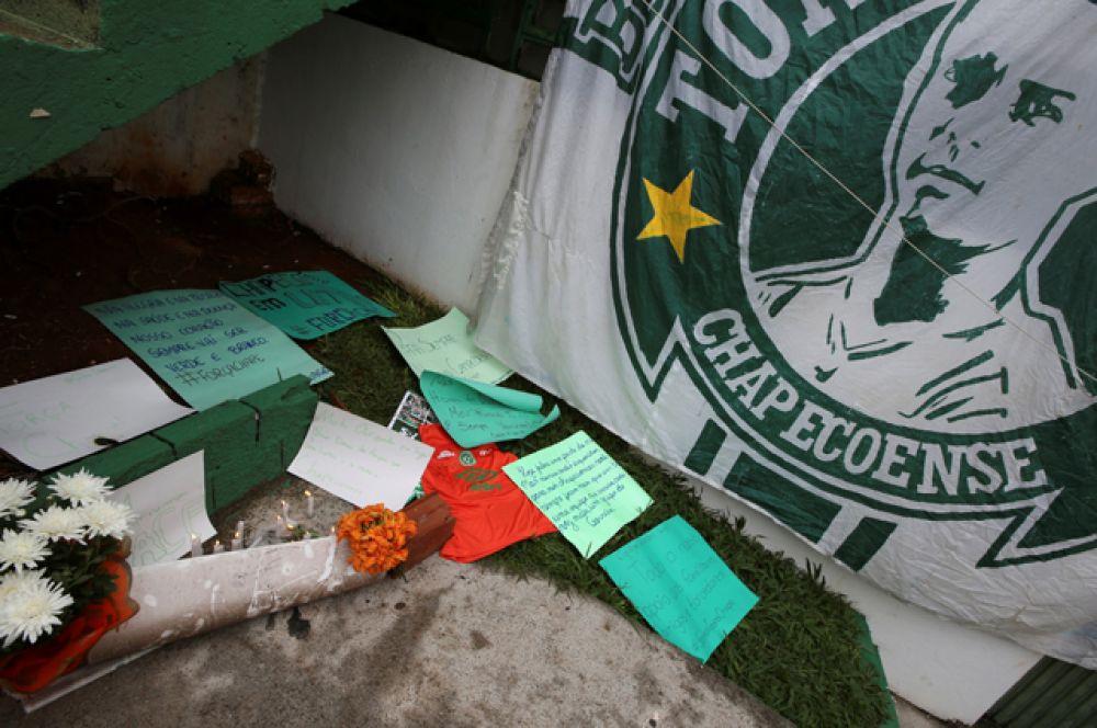 Люди несут цветы и памятные записки к стадиону Арена Конда в городе Шапеко.