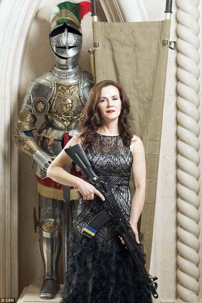 Ксения вместе с автоматом и рыцарскими доспехами на заднем фоне выглядит как настоящий защитник. Кстати платье женщины-военной отлично сочетается с цветом рыцарских доспехов