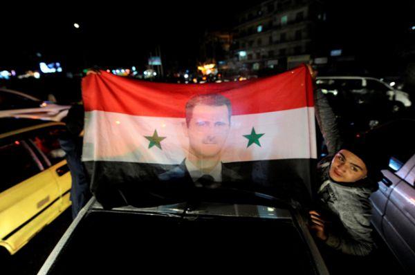 Сторонники президента Сирии Башара аль-Асада несут сирийский национальный флаг с его изображением.