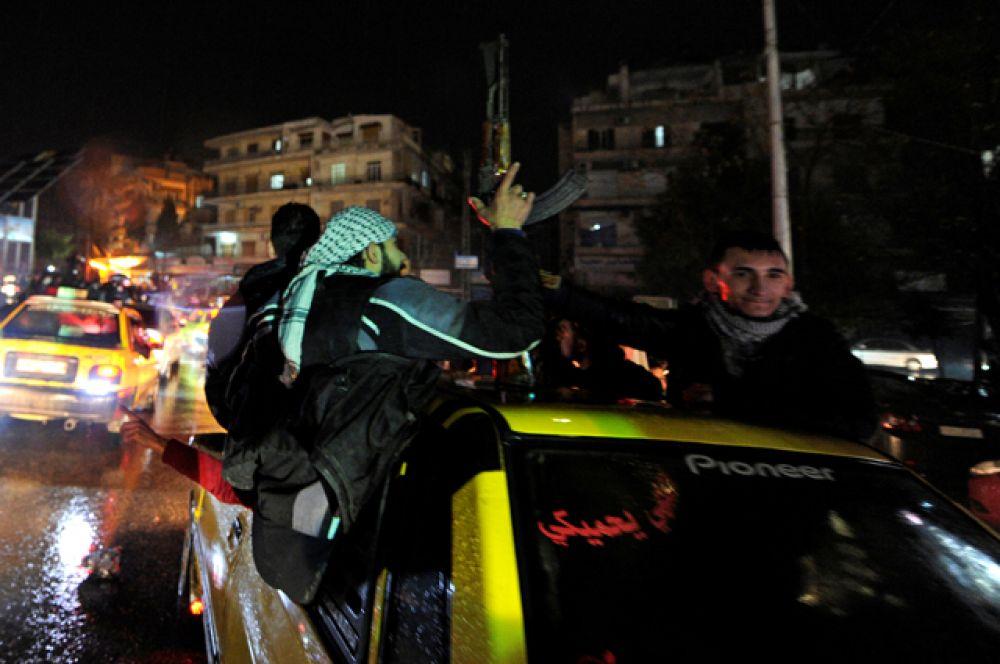 Люди отмечают победу сирийской армии над повстанцами в Алеппо.