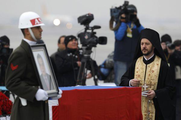 Православный священник произносит молитву над гробом погибшего дипломата.