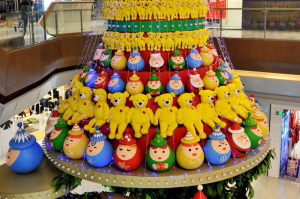 Необычную ель в форме торта из кукол установили в одном из торговых центров Циндао.