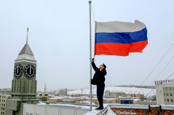 Мужчина опускает российский флаг на крыше здания городской администрации в Красноярске.
