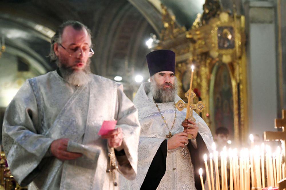 Священнослужители в Богоявленском кафедральном соборе в Москве во время панихиды по погибшим в авиакатастрофе Ту-154 в Сочи.