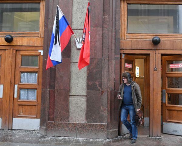 Траурная лента на флаге РФ у станции метро Театральная в Москве в день траура по погибшим в авиакатастрофе в Сочи.