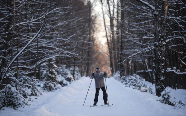 Мужчина катается на лыжах в одном из парков Москвы.