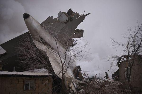 На этом фото видно, что поврежденный хвост самолета застрял в жилом здании