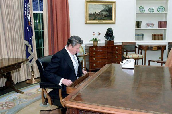 Президент Рональд Рейган сидит за столом в Овальном кабинете после инаугурационного парада в январе 1981 года.