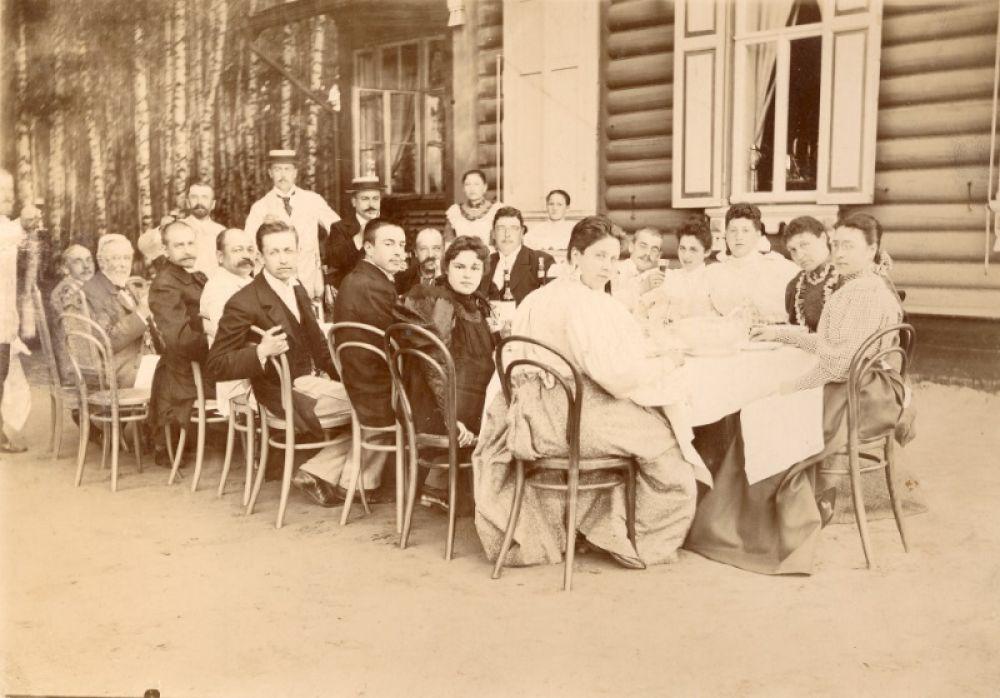 Группа женщин и мужчин, отдыхающих на даче, за праздничным столом