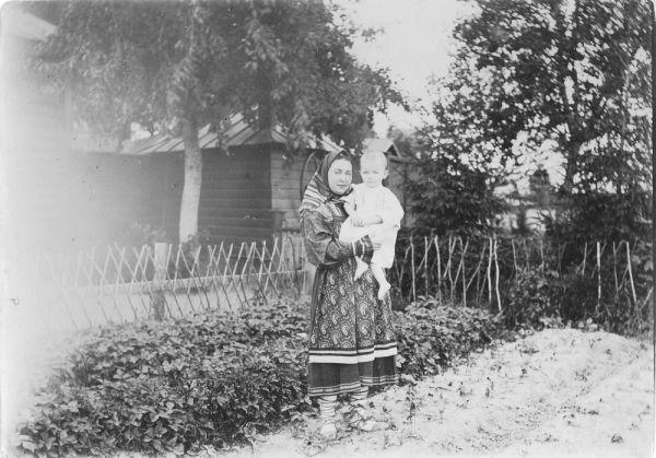 Крестьянка с ребенком на руках около дома.