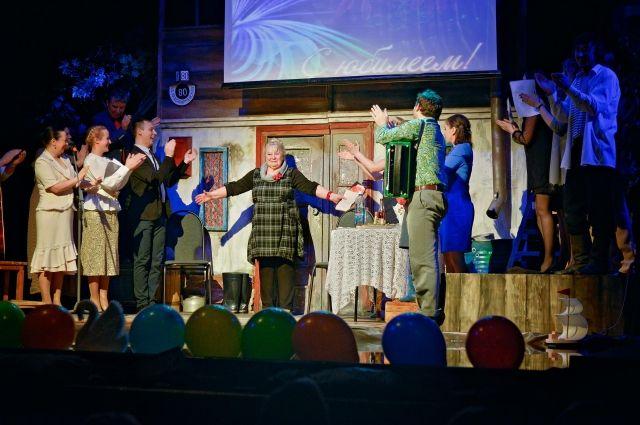 На сцене театра артисты поздравляют юбиляра.