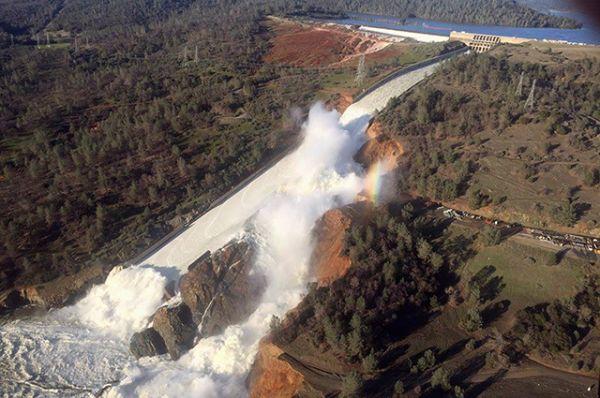 На снимке, сделанном с воздуха над плотиной в Оровилле, виден поврежденный водосброс и размытый склон холма.