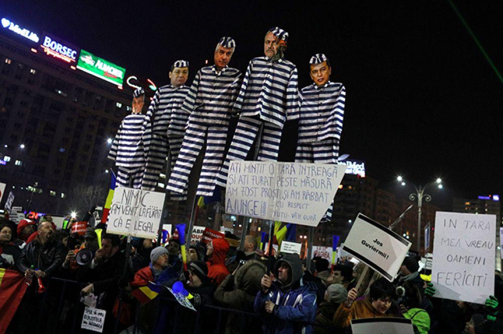 В руках у протестующих румынские флаги и плакаты, на которых написано «Аннулируйте постановление», у некоторых — картонные куклы в виде некоторых членов кабинета в тюремных робах.