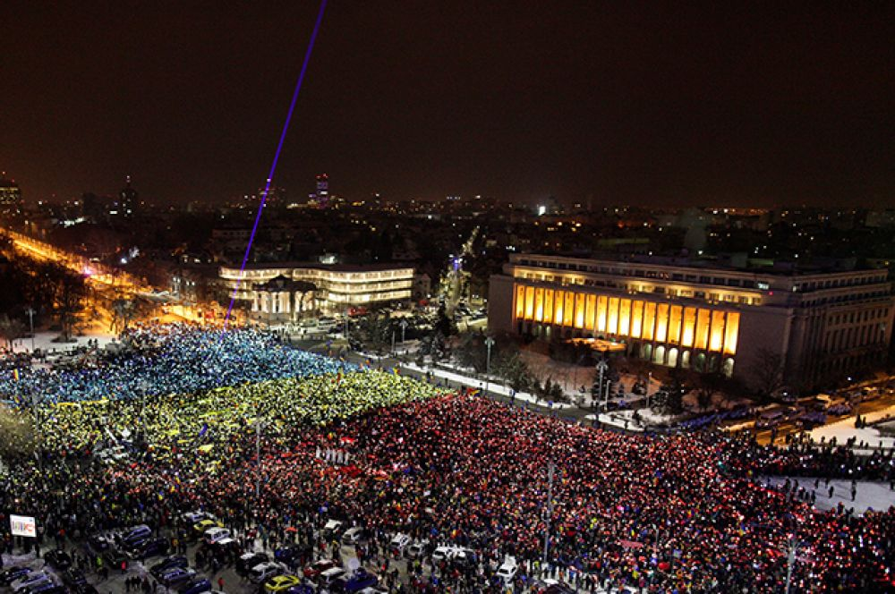 Десятки тысяч участников акций протеста вновь собрались в Бухаресте у здания румынского правительства, образовав гигантский флаг.