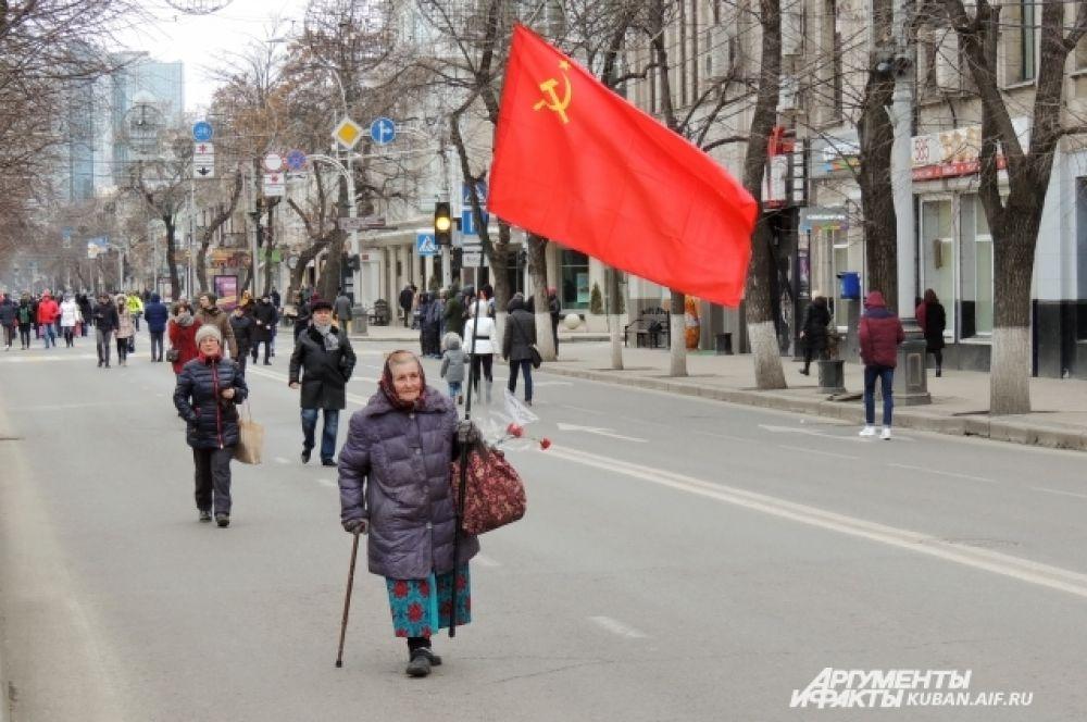 Эта женщина пришла на праздник со своим флагом и цветами.